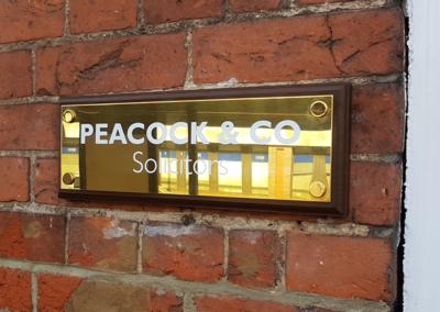 Polished Brass Wall Plaque on Dark Wood