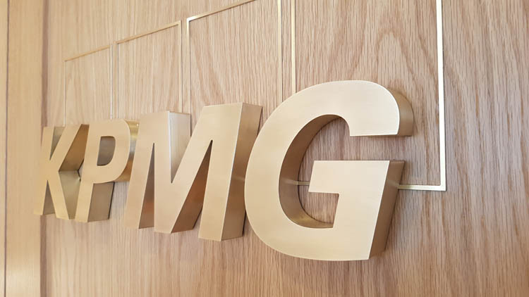 Brushed Brass Letters on a wooden wall at KPMG reception in London - side view