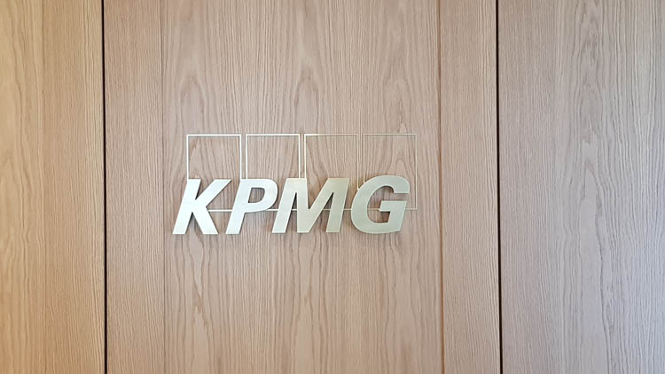 Brushed Brass Letters on a wooden wall at KPMG reception in London - front view