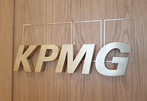 Brushed Brass Letters on a wooden wall at KPMG reception in London